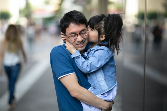 daughter kissing father